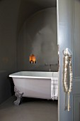 String of stone beads hung on handle of open door showing view of free-standing clawfoot bathtub below illuminated niche in dark grey wall