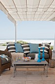 Coffee table in front of sofa with striped scatter cushions below pergola with fabric canopy; beach and sea in background