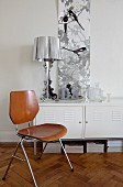Silver table lamp, picture of birds and ornaments on white locker behind retro chair