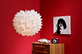 Origami lampshade in front of red walls