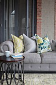 Scatter cushions on grey sofa behind side table