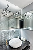 Spherical sink on granite counter against mosaic-tiled wall below designer lamps
