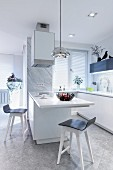 White kitchen counter with protruding table and bar stools in open-plan designer kitchen