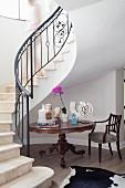 Barocker Tisch mit Skulpturen unter elegant geschwunger Treppe im Eingangsbereich