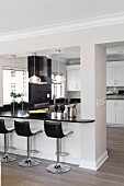 Open-plan, American-style kitchen with black worksurface and breakfast bar with bar stools
