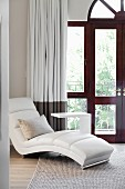 White, modern chaise and purist side table in front of arched balcony door