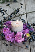 Candle in autumnal wreath of pompom dahlias, hydrangea flowers and sloe branches