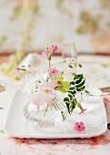 Delicate flowers in glass vase on white ceramic dish