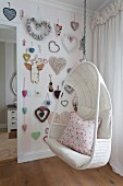 White wicker hanging chair and heart-shaped decorations on wall in girl's bedroom
