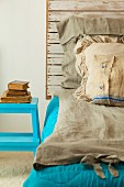 A homemade bed with a rustic wooden headboard and old-fashioned bedclothes
