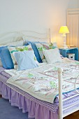 Romantic double bed with ruffled, lilac valance and bedside table made from fruit crate painted light blue