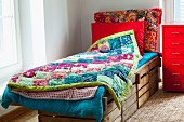 Rustic bed made from wooden crates with colourful patchwork blankets next to bright red metal filing cabinet