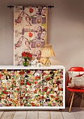 Sideboard with floral doors, classic chair with red shell seat and long fabric wall hanging
