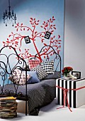 Black and white striped cubic side table next to metal bed against poster of red, stylised tree on wall
