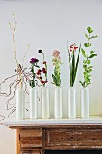 Row of white vases holding single flowers on vintage cabinet