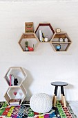 Hexagonal wooden shelving units on wall and on floor next to pouffe and stool