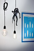 Two purist pendant lamps with illuminated light bulbs and knotted cables, one with Alien figurine