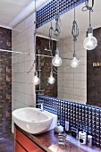 Blue, futuristic, structured wall with mirror and pendant bulb lamps with knotted cables above washstand