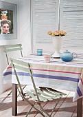 Teekanne und Becher auf Tisch mit gestreifter Tischdecke, hellgrüne Klappstühle