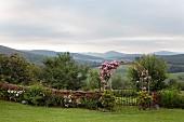 Halbhohe Gartenmauer und Rundbogentor mit rosa Kletterrosen, im Hintergrund Berglandschaft