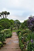 Narrow stone-paved path leading to fountain in flowering garden