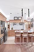 Barhocker und Theke aus hellem Holz in offener Küche in modernem Landhausstil