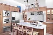 Frühstückstheke und Barhocker in offener Küche aus hellem Holz in modernem Landhausstil