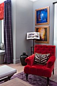 Armchair with red velvet cover in front of gilt-framed artworks on grey-painted wall