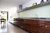 Long, wood-effect kitchen counter below shelf in kitchen with dining area in background in front of terrace doors