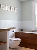 Toilette und eingebaute Badewanne vor weisser, halbhoher Fliesenwand