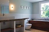 Waschtisch und Toilette vor weisser, halbhoher Fliesenwand, im Hintergrund eingebaute Badewanne unter Fenster