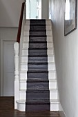 Stairwell with black, runner-style stripe down centre of white, wooden stairs