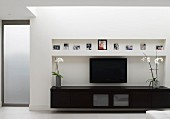 Low, black sideboard and flatscreen TV in niche in contemporary living room