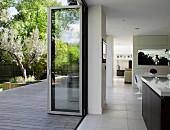 View from open-plan interior through open folding door out onto terrace and into garden