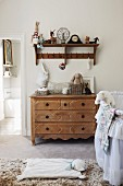 Traditional bassinet, chest of drawers and vintage shelves with hooks in nursery