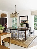 Dark wooden table, Ghost chairs and Persian rug in eclectic dining room