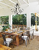 Large dining table and Industrial-style metal chairs on roofed terrace furnished in shades of brown