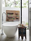 Free-standing bathtub with standpipe tap fitting and Oriental side table in front of floor-to-ceiling window with view of patio