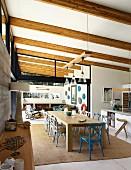 Langer Esstisch aus Holz und Stühle auf Sisalteppich unter Holzbalkendecke