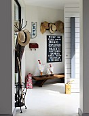 Hats on vintage coat stand and collection of hats on coat rack above hen figurines on bench