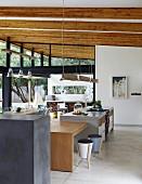 Esstisch aus Massivholz als Erweiterung der Theke in offener Küche mit rustikaler Holzbalkendecke