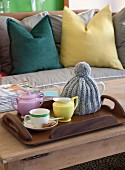 Teapot under knitted cosy and cup on tray in front of brightly coloured scatter cushions on sofa