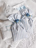 Fabric, scented sachets decorated with satin flowers and embroidered with initials