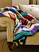 Blanket crocheted from colourful odds and ends of yarn on sofa