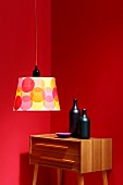 Simple lampshade decorated with colourful circles in front of ceramic bottles on retro chest of drawers against red walls