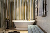 Retro bathtub, side table and upholstered bench in bathroom with striped curtains and marbled wall