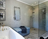 Pale blue upholstered bench between walk-in shower with glass screen and bathtub with bath caddy