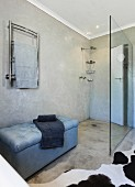 Concrete floor and marbled wall in purist bathroom with walk-in shower and upholstered bench