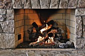 Fire in rustic open fireplace with stone surround