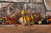 Autumnal arrangement of pumpkin, sprigs of berries and leaves against stone wall